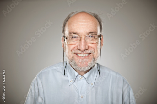 Portrait of old man taking glasses and smiling