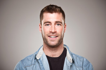 Portrait of a normal young man smiling over grey background.