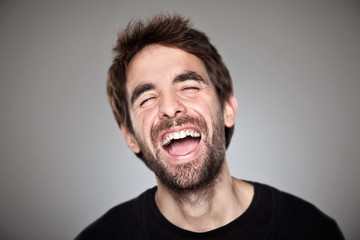 Portrait of a normal boy laughing isolated on white