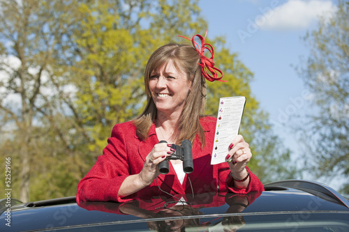 Female racegoer viewing a race from a car roof