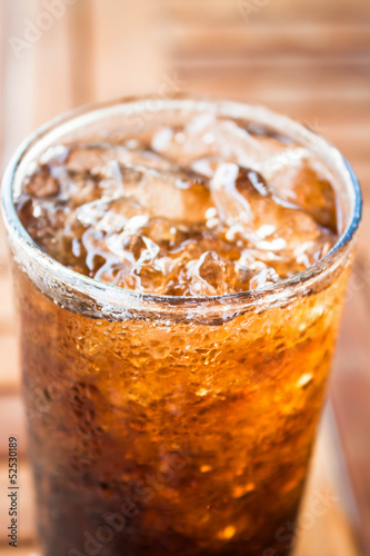 Close up cola drink with ice on wood background