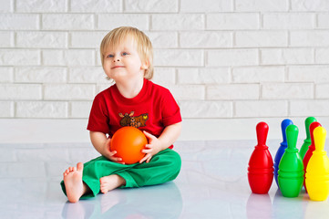 Baby boy playing with colorful plastic toy bowling