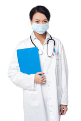 Surgeon holding clipboard. Face covered with surgical mask