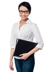 Smiling female executive holding business files