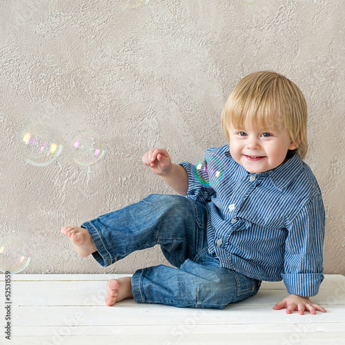 Nice kid playing with soap bubbles in studio