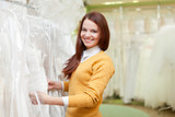bride chooses gown at shop of wedding fashion