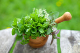 fresh herbs in a wooden mortar