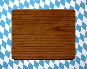 Braunes Holzbrett auf bayrischem Rauten-Hintergrund