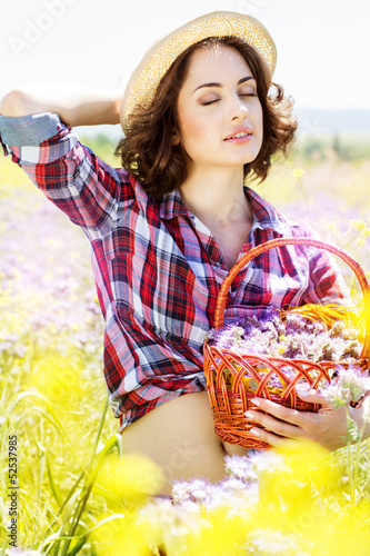 Portrait of young woman holding basket with flowers outside