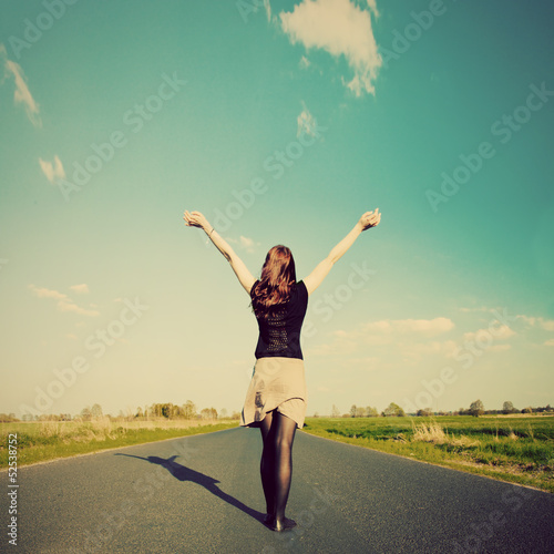 Happy woman standing on empty road. Retro vintage style