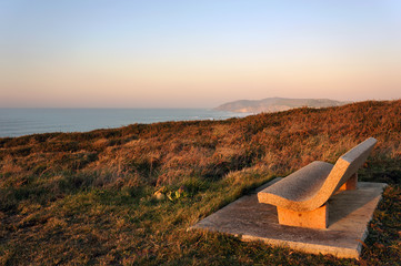 stone bench near sea at sunset
