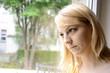 Junge Frau schaut traurig aus Fenster