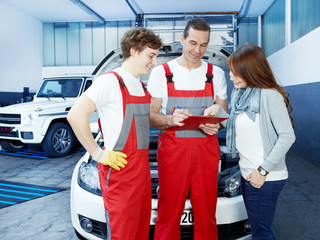 Customer and mechanics in a garage looking at a quotation