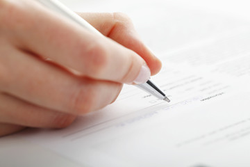 Businesswoman writing on a form