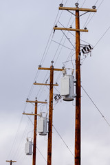 Row of utility poles power cables and transformers