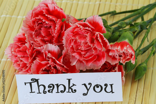 Thank you note and red and white carnations on bamboo mat