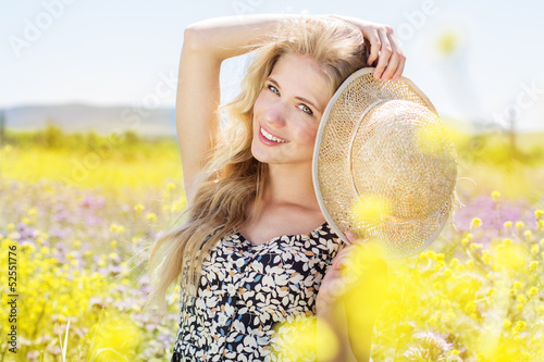 Portrait of young woman in the flowers field