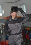 Smiling welder in gray workwear and helmet at work place poster