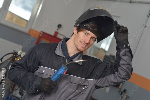 Smiling welder in gray work wear and helmet at work place