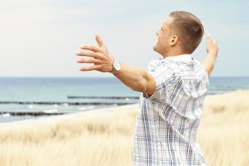 Mann am Meer breitet Arme aus