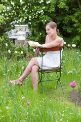 Frau im Garten sitzend und in einem Buch lesend