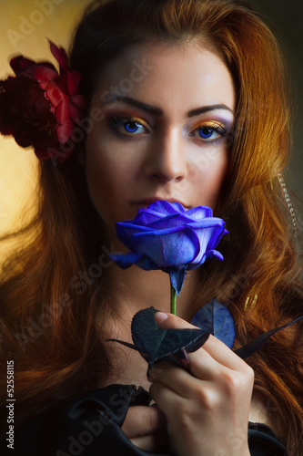 beautiful woman with red rose and blue lights.
