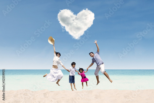 Happy family jumping under love cloud at beach