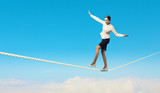 Businesswoman balancing on rope