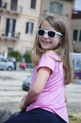 Smiling Little Girl With Sunglasses Riding a Pony