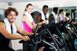 Group of friends cycling in gym