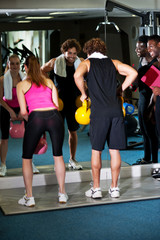 Fitness trainer giving out instructions to people