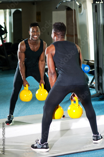 Young muscular man working out with kettlebell