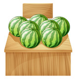 A watermelon stand with an empty wooden signboard
