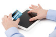 Man's hand holding a credit card over a tablet computer and the