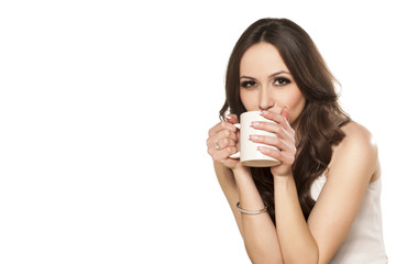 girl enjoys her cup of tea on white background