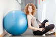 Young woman doing exercise with a gym ball