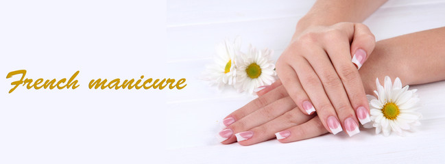 Woman hands with french manicure and flowers