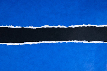 Torn blue paper with black space