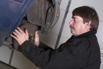 Automotive Technician Manually Pulls Rotor Checking Brakes Auto