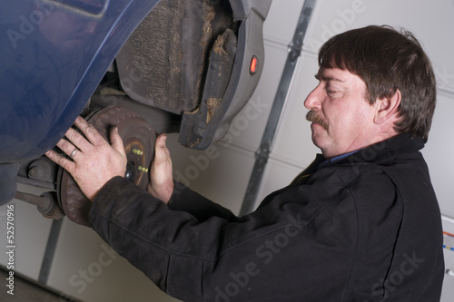 Automotive Technician Manually Pulls Rotor Checking Brakes Auto