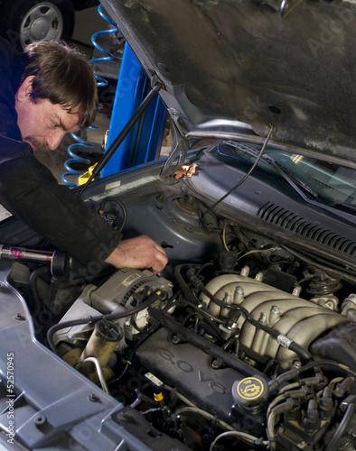 Automotive Technician Works Under the Car Hood in Auto Repair