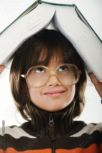 Student child with a book and glasses over his head isolated ove
