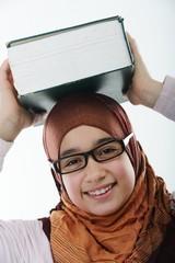 Female Arabic student balancing big book on head