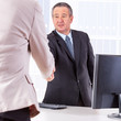 Businessman in office ranges woman's hand