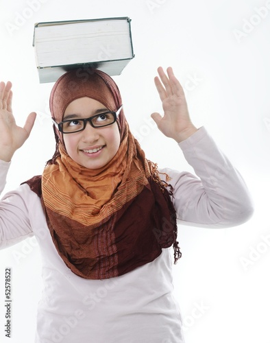 Female Arabic student balancing big book on head