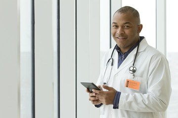 African American doctor smiling and holding a tablet