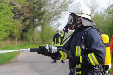 Feuerwehrmann mit Schlauch in der Hand