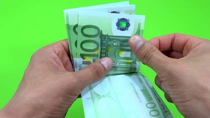 person counting euro in green background