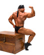 Bodybuilder sitting on a wooden chest