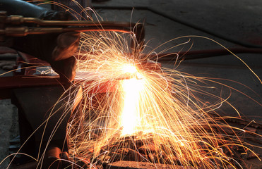 Industrial worker cutting steel by using metal torch